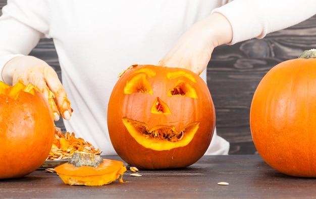 Женщина вырезает тыкву для празднования хэллоуина, несколько оранжевых тыкв небольшого размера на столе