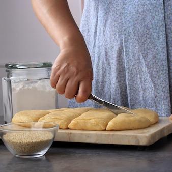 女性はパン生地をカットし、キッチンで焼くプロセス。 odading / roti bantal / golang galing / bolang baling、インドネシアのバンドンのバイラル屋台の食べ物を作る