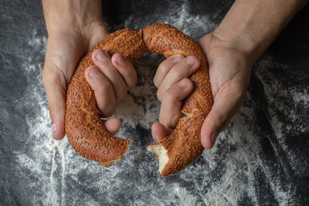 Woman cut simit in half with hand.