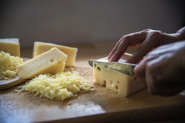 Woman cut slice cheese for cook using knife in the kitchen - people making food with cheese concept