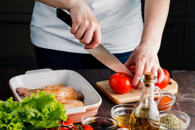 Женщина вырезать помидор для приготовления курицы