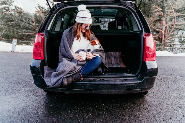 Woman and cute jack russell dog enjoying outdoors at the mountain into the car. travel concept. winter season