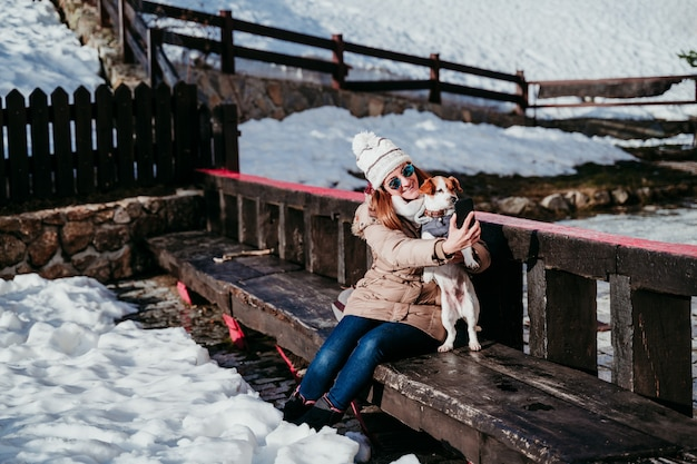 Woman and cute jack russell dog enjoying outdoors at the mountain with snow. winter season. woman taking self portrait with mobile phone