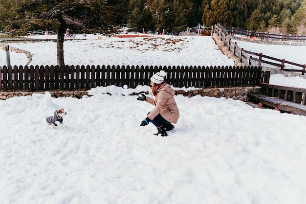 Woman and cute jack russell dog enjoying outdoors at the mountain with snow.