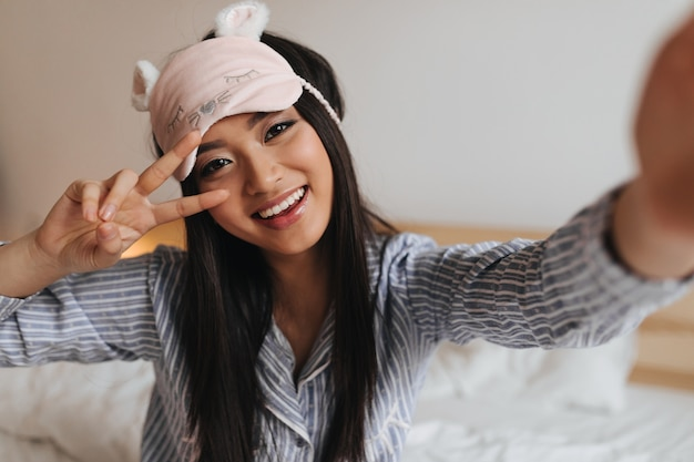 Woman in cute sleeping mask shows sign of peace and makes selfie in bedroom