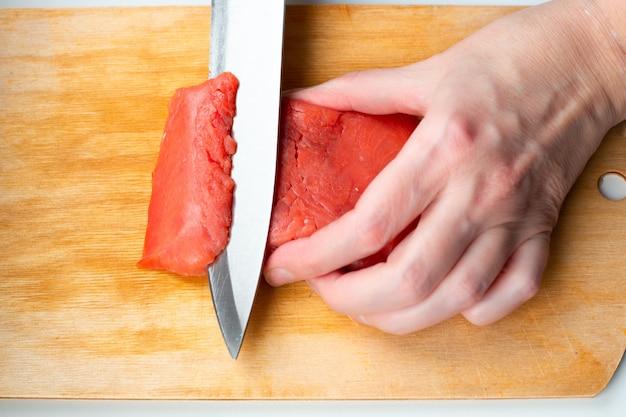 Женщина режет ножом кусок красной рыбы на деревянной разделочной доске