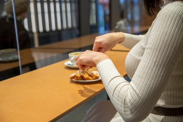 Женщина режет круассан и пьет кофе за столиком в кафе. без лица