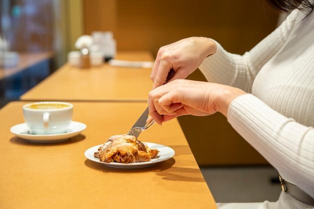 Женщина режет круассан и пьет кофе за столиком в кафе