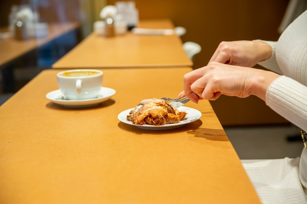 Woman cuts croissant and drinks coffee at a table in a cafe. no face