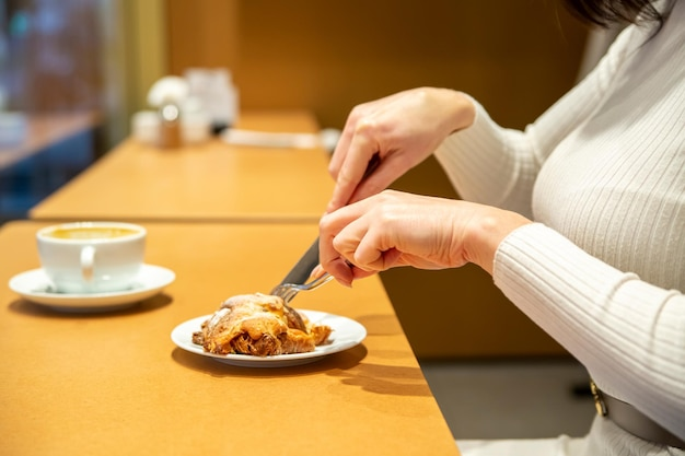 Woman cuts croissant and drinks coffee at a table in a cafe
