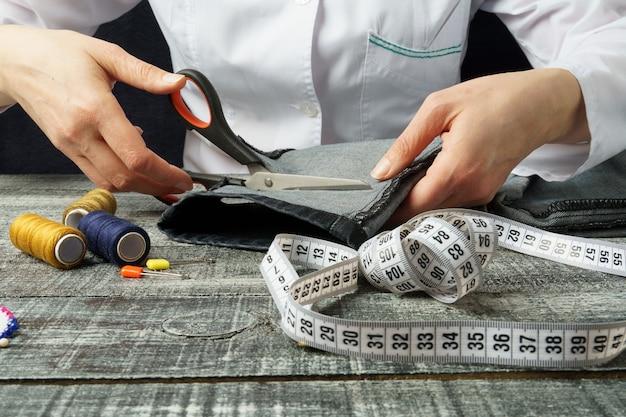 Женщина разрезает джинсовую ткань ножницами ножницы разрезает джинсы портниха на рабочем месте