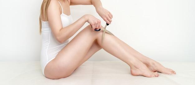 Женщина стрижет ножницами волосы на ногах