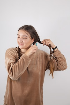 A woman cuts her long hair. cardinal shocking image change