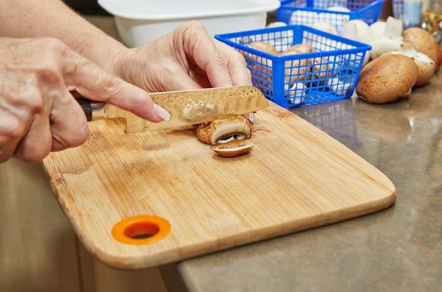 Женщина режет грибы на деревянной разделочной доске. готовит по рецепту в домашних условиях на кухне