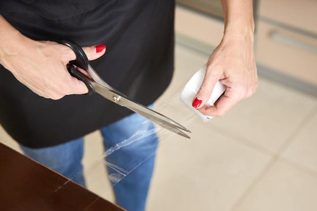 Женщина отсекает часть клейкой ленты, необходимой для упаковки товаров