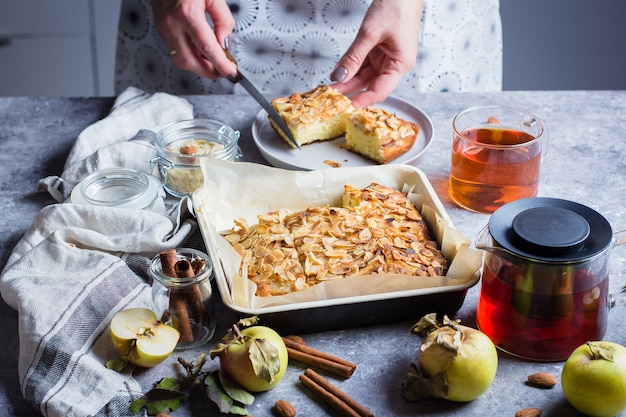 Woman cuts piece of homemade apple pies. norwegian biscuit pie on stone concrete table bac
