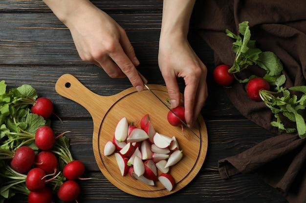Женщина режет редис на разделочной доске на деревянном столе