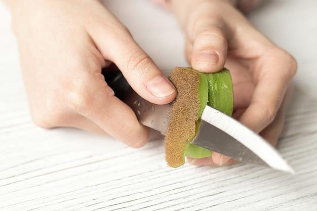 Женщина режет спелый киви, крупным планом