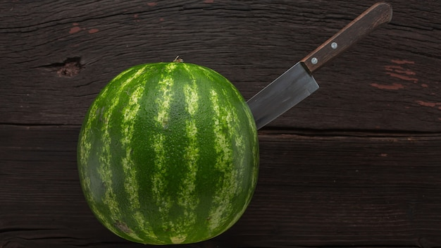 Woman cuts ripe watermelon on a wooden table