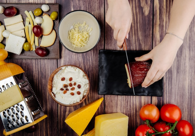 A woman cuts smoked cheese on a black tray cottage cheese in a bowl grater pickled olives and fresh tomatoes on rustic top view