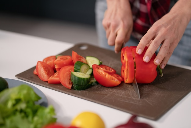 Женщина режет овощи для свежего салата, режет на борту, готовится к обеду