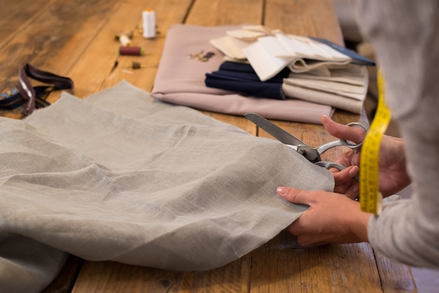 ファッションスタジオのテーブルで布を切る女性。テーブルの上のはさみの生地を扱う女性のテーラー。生地のパターンを作る仕事で仕立て屋のクローズアップ。