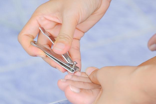 つま先の爪を切る女性