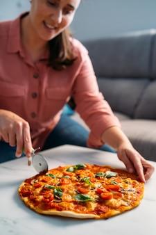 彼女のリビングルームで伝統的なイタリアのマルガリータピザを切る女性