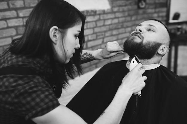 Woman cutting beard of man