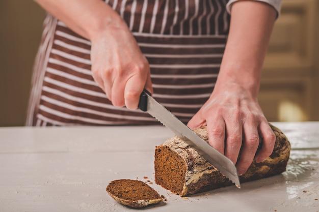 Женщина резки хлеба на деревянной доске. пекарня. производство хлеба. женщина в полосатом фартуке