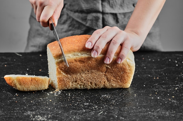 Woman cutting bread with knife on dark desk.