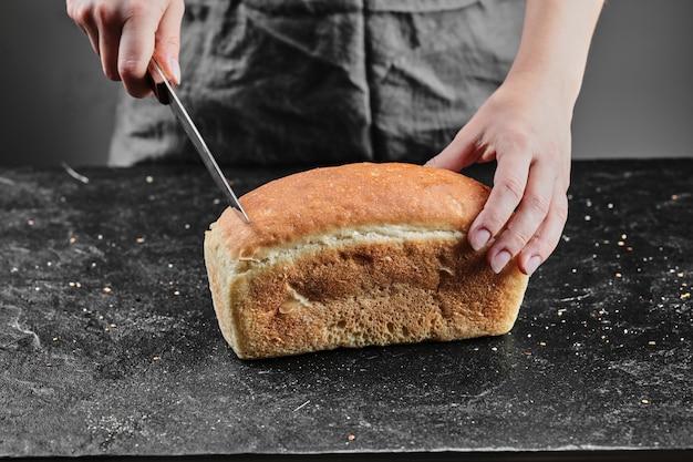 Женщина резки хлеба с ножом на темном столе.