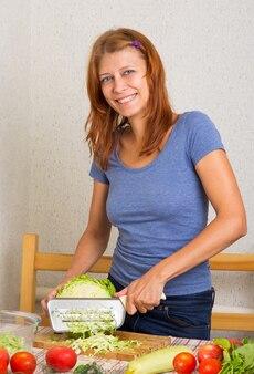 キッチンでキャベツを切る女性