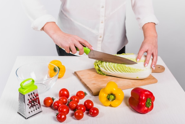 Woman cutting cabbage on wooden board
