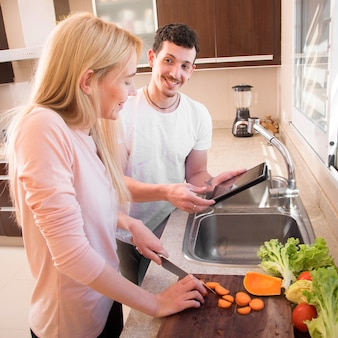 Woman cutting carrot on chopping board looking at digital tablet hold by his friend