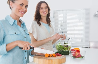 Woman cutting carrots with her friend mixing salad