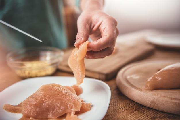 Woman cutting chicken meet