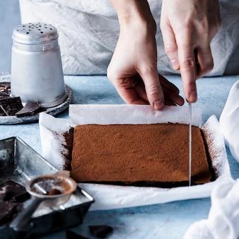 キッチンでチョコレートガナッシュトリュフの正方形を切る女性