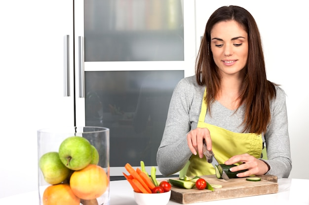 Woman cutting cucumber and vegetables in kitchen