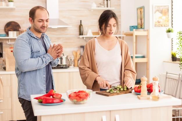 夫と会話しながらキッチンでヘルシーサラダのためにきゅうりを切る女性。幸せな恋の陽気でのんきなカップルが食事を準備するために互いに助け合っています