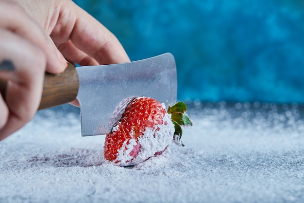 Woman cutting fresh strawberry on blue surface with knife