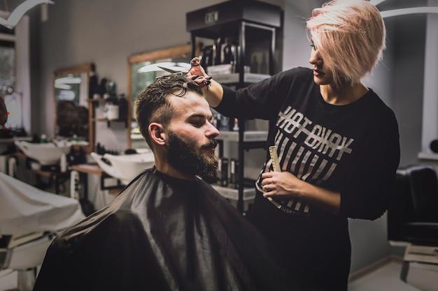 Woman cutting hair of man in salon
