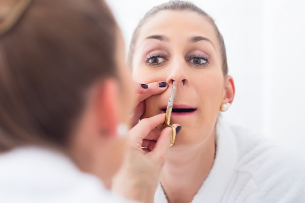 Женщина подстригает ноздри