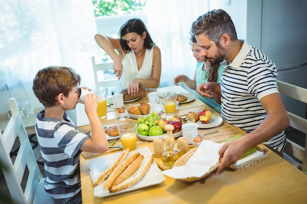Woman cutting loaf of bread while family having breakfast