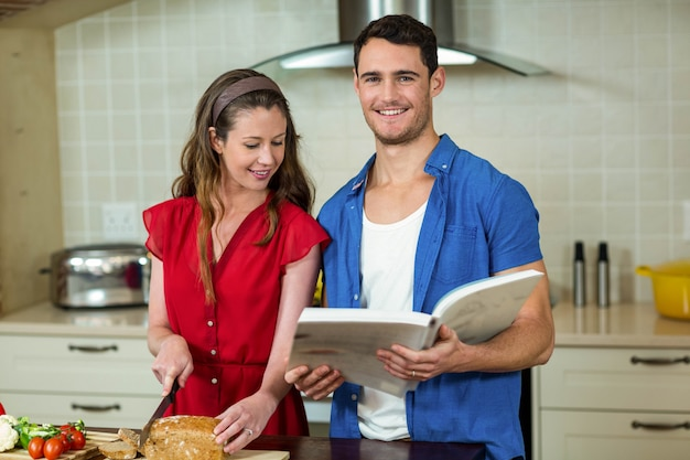 Woman cutting loaf of bread while man checking the recipe book in kitchen at home