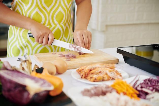 Женщина режет стебель лотоса