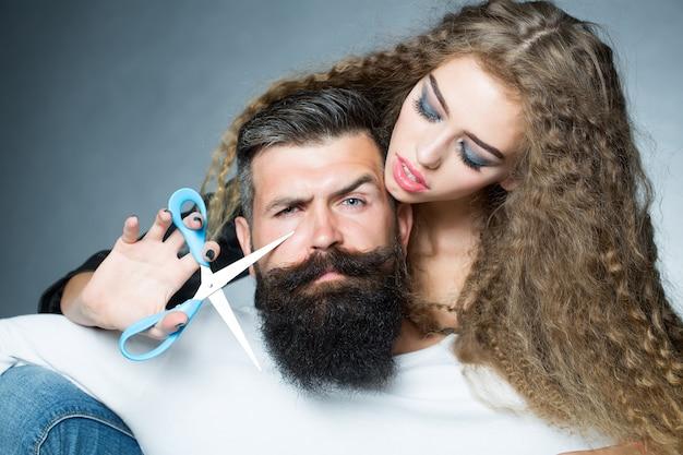 Woman cutting mans beard Premium Photo
