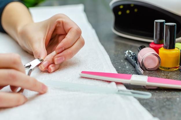 Женщина, режущая ногти кусачками - крупный план. домашний уход за ногтями.