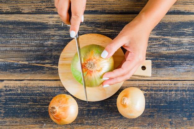 Woman cutting onion using knife