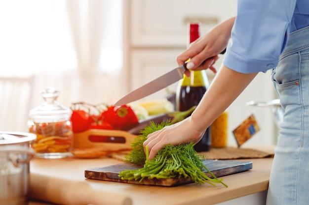 キッチンで木の板にパセリを切る女性
